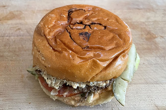 A cheeseburger branded by a Sam the Cooking Guy logo