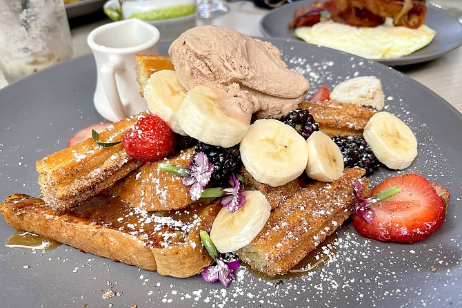 Churros and French toast, topped with fruit, caramel sauce, and dulce de leche ice cream