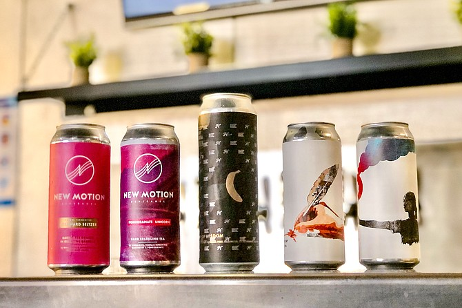 Cans of New Motion hard seltzer and hard tea, alongside cans of Embolden Beer Co. Both now brewed in Miramar.