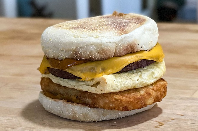 A vegan breakfast sandwich, with plant based eggs, sausage, and cheese, plus air-fired hash browns and maple chipotle sauce