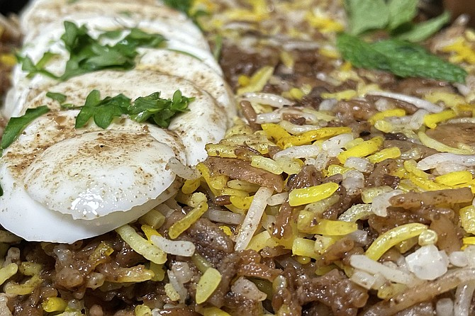Lamb biryani with egg, almonds, raisins, and saffron rice