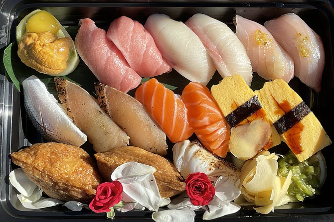 "A box of ""bomb cuts"" sushi. Top row (left to right): Uni and quail egg, bluefin tuna belly, yellowtail belly, white sea bass. Middle row: gizzard shad, seared albacore, Atlantic salmon, tamago. Bottom row: crab inari, seared sea bream, pickled wasabi)."