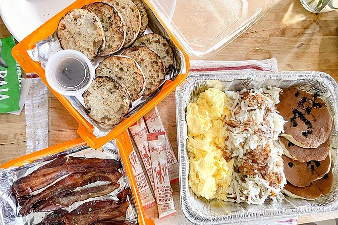 A family meal bundle from Snooze, with eggs, bacon, hash browns, toast, and blueberry pancakes.