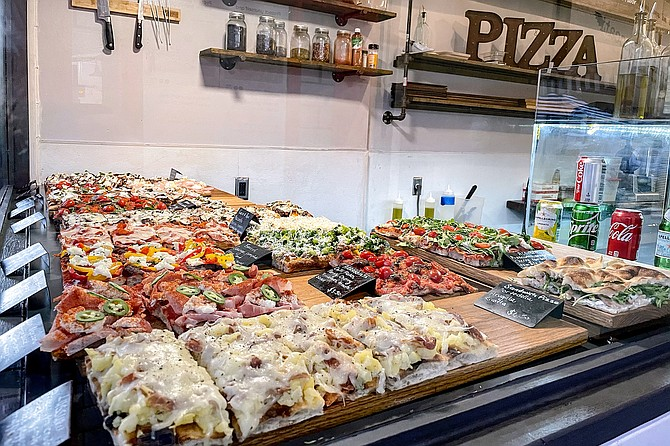 Roman pizza, also known as pinsa, slices arranged in the window of Gelati & Peccati