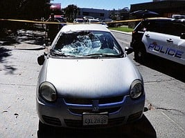 Evidence photo of the car w smashed windshield, it contains the officer's radio.