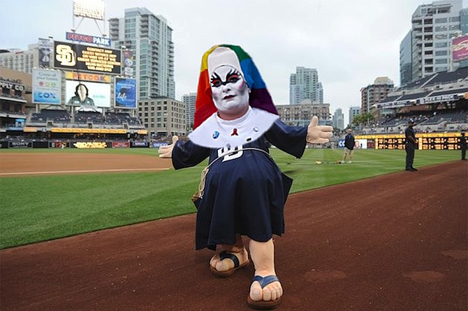 """The Swinging Sister, new mascot for San Diego's baseball team, rechristened from Padres to Drag Queens. Explained Padres owner Ken Craven: """"After the city changed its name, it really didn't make sense to have a team named after Franciscan priests, no matter how effective they were at subjugating others. But then someone in the uniform design department suggested that we could keep with the religious theme, while at the same time honoring both the fabulous character of our new city name and the heroic struggle of the LGBTQIA+ community. And so, the San Diego Drag Queens are proud to announce that their new mascot is a member of the Sisters of Perpetual Indulgence. Slay, Queens!"""""""
