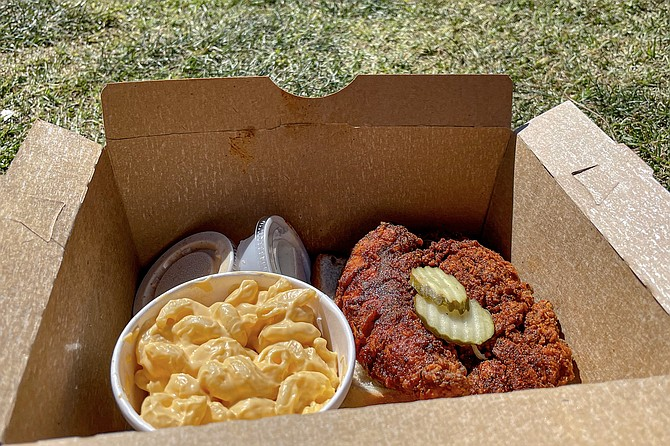 An extreme chicken tender with a side of macaroni, in a box ready to picnic