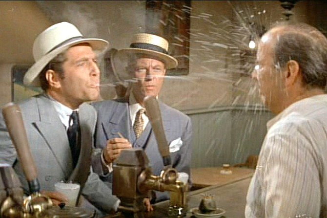 The St. Valentine's Day Massacre: George Segal dots the barkeep's eye with a shot of Cagney Spritz on the house.