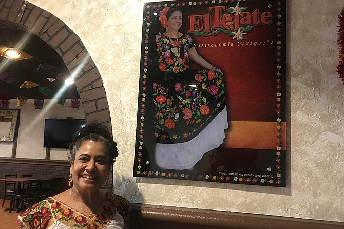 Survivor - Owner Lucy Contreras, and poster showing her in traditional Oaxacan dress.