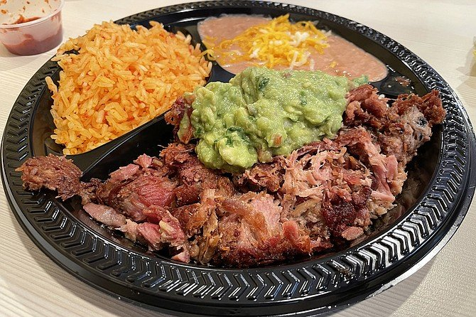 Carnitas combo, with guacamole, red rice, refried beans, and corn tortillas