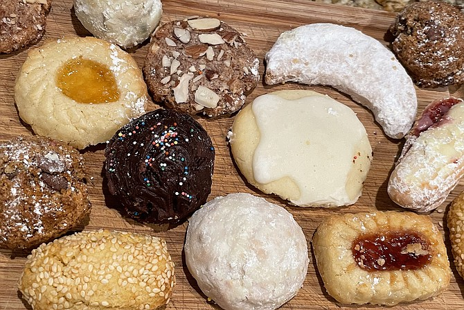 Italian cookies, including lemon and chocolate ricotta cookies (center), sugar dusted snowballs with nuts, Sicilian chocolate chip (top right and bottom left), and more