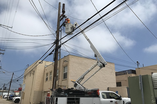 Jeff attaches cables. Above him, the 4G transmitter cell he is installing. Is the apartment below safe?