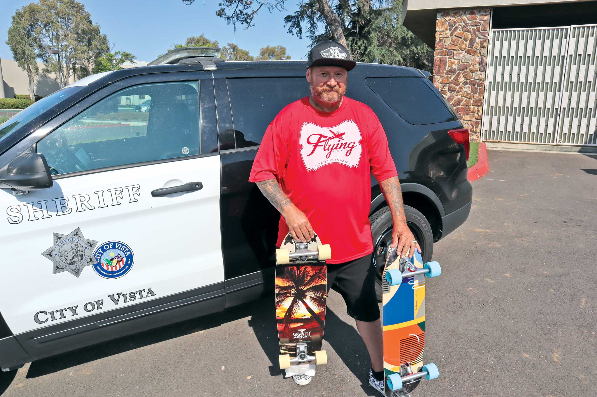 Dennis Martinez with skateboards and Vista Sheriff vehicle CREDIT Chris Ahrens.