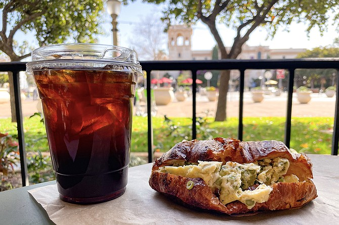 Cold brew and an egg croissant featuring asparagus and green beans